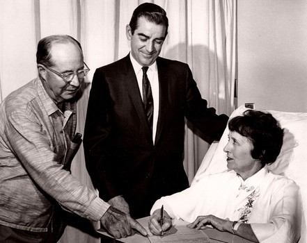 Happy husband and doctor at female patient's bedside, filling out Medicare forms